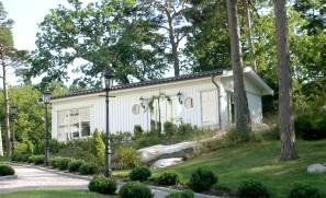 Pavillon en ossature bois avec bardage lasuré blanc.